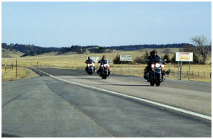 Bikers ride across the stateline of South Dakota into Wyoming.